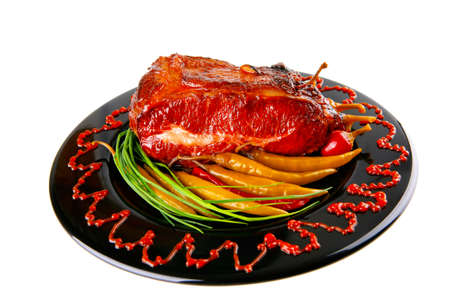 bloc: roast red beef meat bbq bloc served on black plate  with green chives adn red hot pepper on black plate isolated over white
