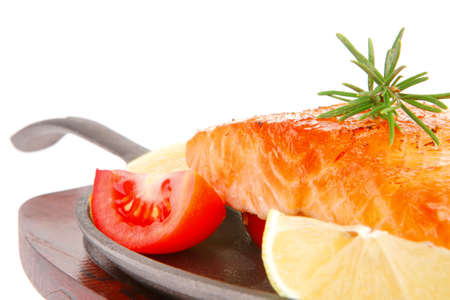 diet healthy food: hot grilled sea salmon fillet served on iron pan over wooden plate isolated on white  photo