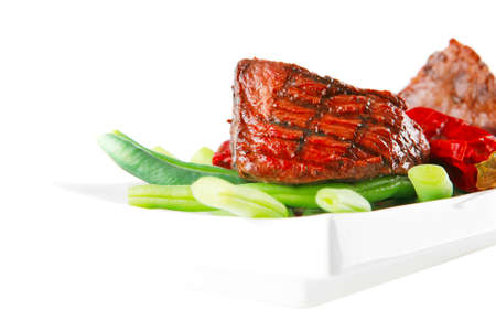 served grilled beef veal fillet entrecote on a white plate with peppers and green peas on long plate isolated on white Stock Photo - 27181049