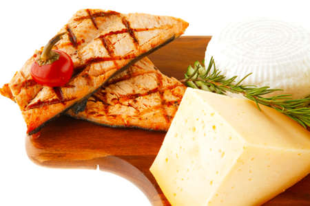 grilled sea fish salmon with french edam gorgonzola and soft feta goat cheeses on wooden plate isolated over white