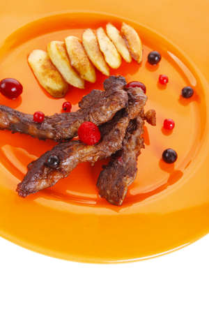 grilled beef meat with berries fried potatoes and cherry under sweet honey sauce on orange plate isolated over white  photo