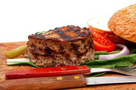 extra thick hot beef meat hamburger lunch on wooden plate with tomatoes and salad isolated on white  photo