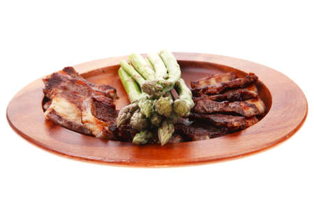 dinner of hot grilled beef meat ribs served with asparagus on wooden plate isolated on white background photo