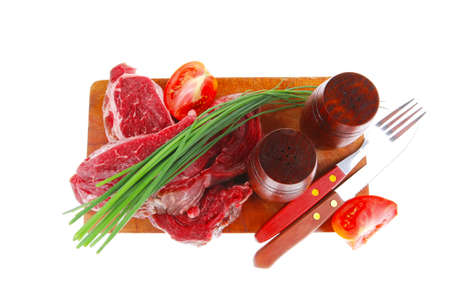 main course : fresh raw beef steak entrecote ready to prepare on cut board with green chives and tomatoes isolated on white  Stock Photo
