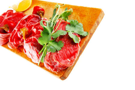 fresh raw beef meat medallion chunks on wooden plate isolated over white background with red hot peppers photo