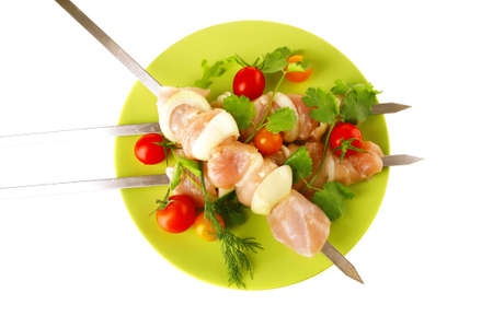 raw uncooked chicken shish kebabs with tomatoes on metal steel skewers on green plate isolated over white  photo