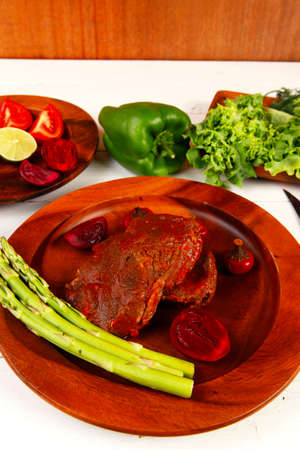 grilled roast red beef meat served on wooden dishes with peppers cutlery salad and vegetables on white wooden table photo