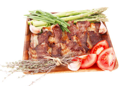 fresh grilled meat beef ribs with asparagus thyme and tomatoes on wooden plate isolated over white  photo