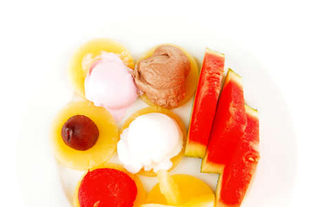 watermelon plum and slice of pineapple and chocolate and fruit ice cream on white plate isolated over white