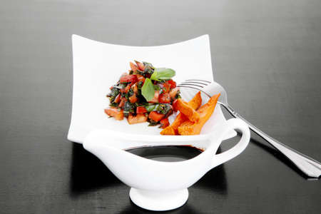 vegetable salad : cherry tomatoes and basil with sweet baked potato served on white plate with sauceboat full blask soy sauce on wood photo