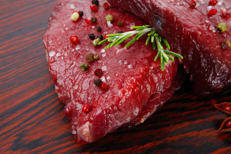 fresh raw beef fillet mignon on old retro style wood as background with rosemary peppercorn and salt photo