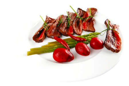 grilled red beef meat rolls with asparagus and hot spices on china plate isolated over white background photo