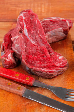castors: fresh raw uncooked beef fillet mignon entrecote on board prepared for cooking on wood table wtih cutlery and castors