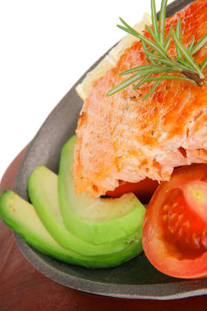 healthy diet food: hot sea grilled  red salmon fish fillet with lemon avocado and tomatoes on metal pan over wooden plate isolated on white  photo