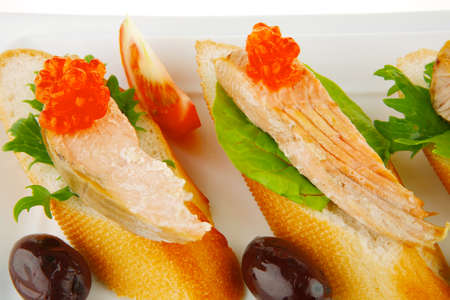 king salmon: healthy appetizer : sandwich with sea salmon and red caviar, olives, tomato and lemon on white china plate isolated over white  Stock Photo