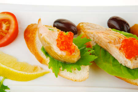 healthy appetizer : sandwich with sea salmon and red caviar, olives, tomato and lemon on white china plate isolated over white  Stock Photo