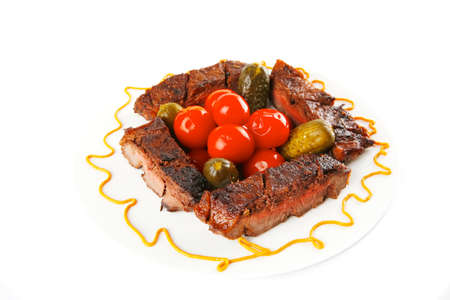 roast beef meat steak with cherry tomatoes and salted cucumbers on white plate isolated over white  photo