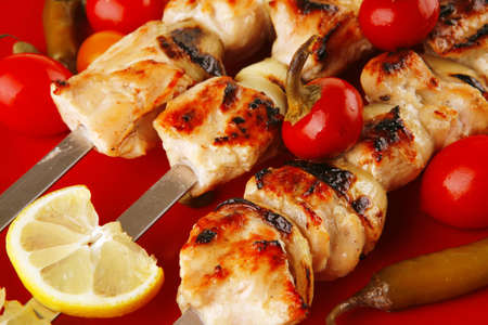 fresh grilled chicken shish kebab served wtih tomato cherry hot peppers on skewers over red plate isolated on white background photo