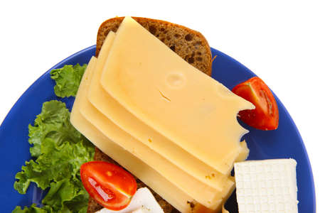 set of gourment cheese slice and chunk   bar   white goat greek yellow french aged on half of rye bread on green lettuce salad with tomatoes on blue plate isolated over white background photo