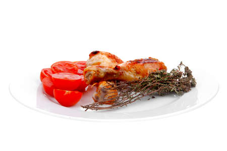 grilled chicken drumstick with tomatoes and thyme on white plate isolated over white background photo