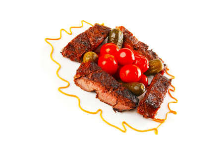 roast beef meat steak with cherry tomatoes and salted cucumbers on white plate isolated over white background photo
