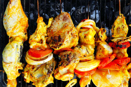 fresh raw roast shish kebab on barbecue grill grid coocked over hot charcoal photo