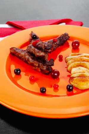 grilled beef meat with berries fried potatoes and cherry under sweet honey sauce on orange plate over black wooden table photo
