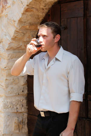young happy white caucasion man taste and enjoy red wine outdoor in in countryside . classic style fashion. photo