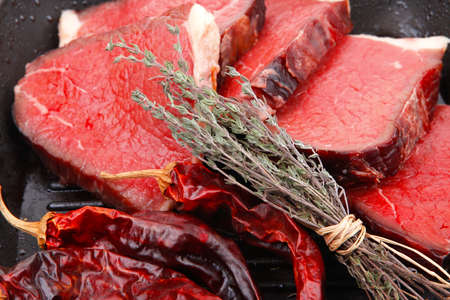 bloody raw beef meat on bbq pan with pepper and thyme isolated on white background photo