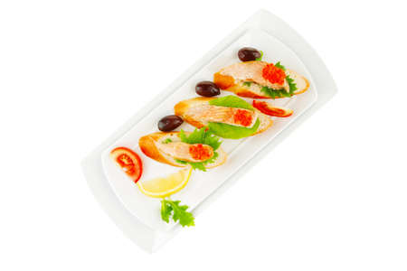healthy appetizer : sandwich with sea salmon and red caviar, olives, tomato and lemon on white china plate isolated over white background photo