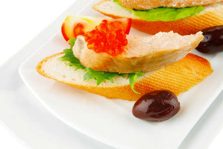 healthy appetizer : sandwich with sea salmon and red caviar, olives, tomato and lemon on white china plate isolated over white background Stock Photo
