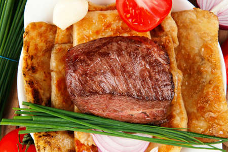 meat grilled: meat : grilled beef fillet mignon on bread with tomatoes salad on wooden table Stock Photo