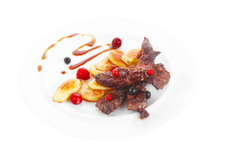 grilled beef meat with berries fried potatoes and cherry under sweet honey sauce on white plate isolated over white background photo