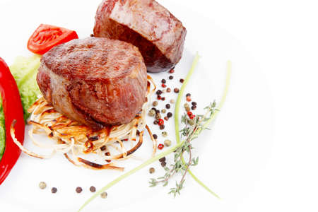 grilled beef fillet with thyme , red hot chili pepper and tomato on plate isolated over white background photo