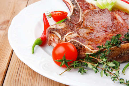 meat food: meat food : roast rib on white dish with thyme pepper and tomato on wooden table