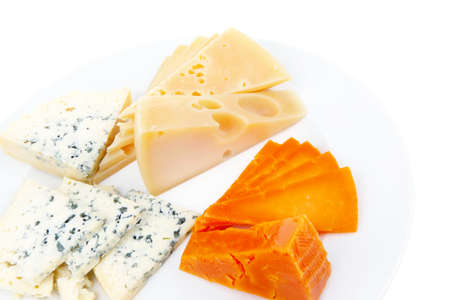 sustained: old blue stilton roquefort with orange cheddar and yellow parmesan and slices on plate with isolated over white background