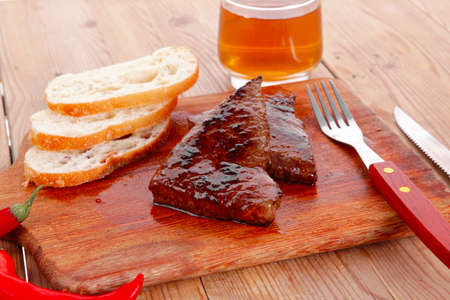 fresh beef meat steak with red hot pepper and bun slices served on plate with whiskey on wood over table with cutlery photo