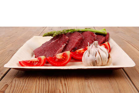 fresh raw beef meat steak fillet on wooden plate with asparagus and tomatoes ready to prepare photo