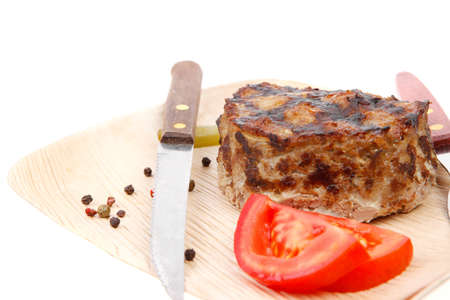 extra thick hot beef meat hamburger lunch on light wooden plate with tomatoes salad and cutlery isolated on white background photo