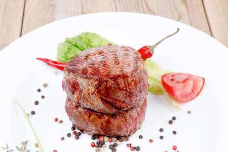 grilled beef fillet medallions with thyme and red hot chili pepper on white plate over wood table photo