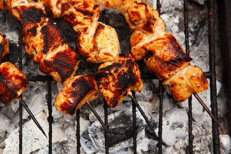 fresh hot grilled chicken shish kebab barbecue on grid over charcoal photo