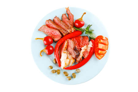 bacon meat slices served with tomatoes capers and red hot chili peppers on blue plate isolated on white background photo
