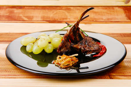 roast ribs on wooden table with grapes photo