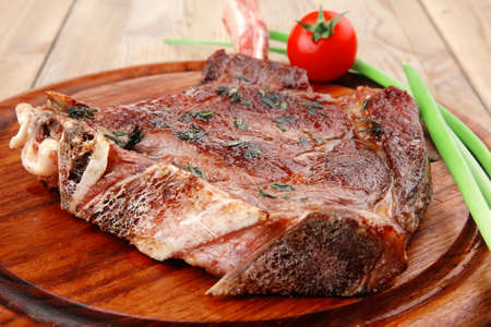 meat savory : grilled beef ribs served with green chives and cherry tomato over wood . shallow dof photo