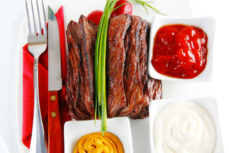 roast red beef meat fillet with red hot pepper with ketchup mayonnaise and mustard on plate isolated on white background photo