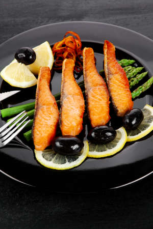 grilled salmon slices with asparagus lemon olives and cutlery on black plate over dark wooden table photo