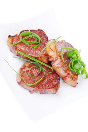 grilled meat beef steaks strips on white plate isolated over white background photo