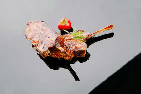 served savory plate: meat ribs with spices and red hot pepper photo