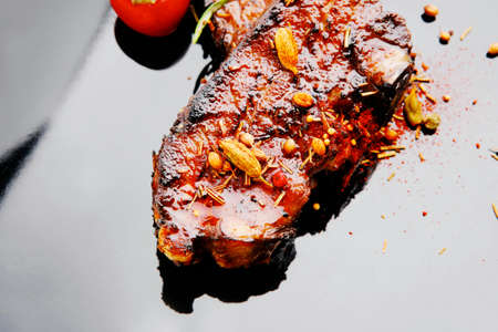 entree: served entree: ribs on plate with spices and red pepper . shallow dof