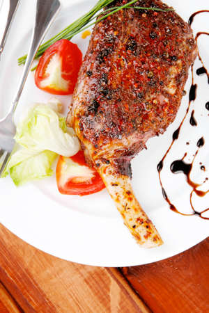 pepper castor: meat on wooden plate : roast shoulder on wood with tomatoes chives and green lettuce on white plate